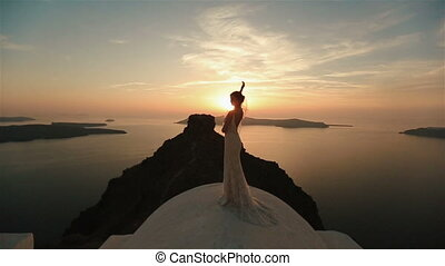 Charming brunette bride enjoying the view on church roof at sunset sky background.