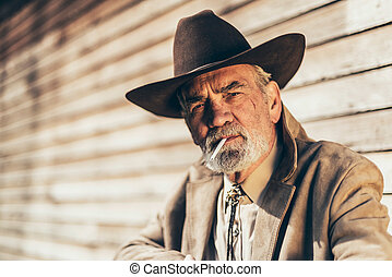 Senior man smoking a cigarette with a pensive look - Senior...