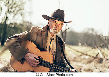 Serious elderly Country and Western guitarist sitting...