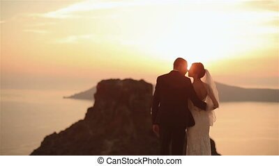 Happy married couple kissing  on church roof at sunset sky background