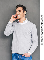Nice to hear your voice! Confident cheerful young man talking on mobile phone and keeping hand in pocket while standing against grey background
