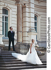 Newlywed couple posing near old building, bride walking down...