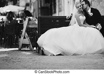 Romantic newlyweds kissing on wooden bench in old french...