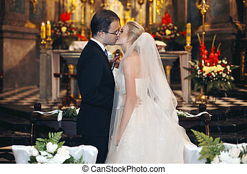 Newlywed bride and groom first kiss at wedding ceremony in church