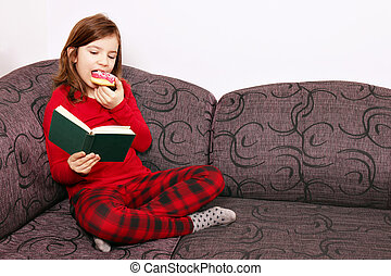 Little girl reading a book and eating a donut
