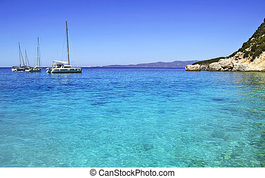 sailboats in Ithaca Greece - sailboats in turquoise sea of...