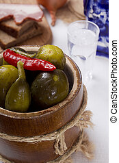 Pickles in a wooden barrel with a red hot pepper