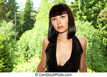 The girl in a black dress against green forest background