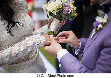 Handsome groom putting on ring on bride at wedding aisle closeup
