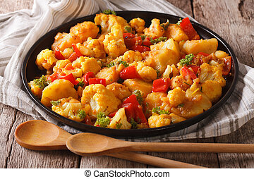 Indian food: vegetarian Gobi Aloo close-up on the table....