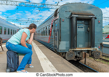 woman sitting on a suitcase and looking at the departing...