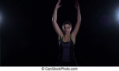 Sporty woman jumps of darkness in gym, slow motion