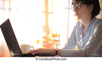 Brunette businesswoman typing on her laptop