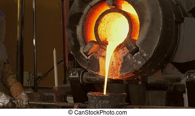 Lost wax bronze casting - pouring the molten metal in the...