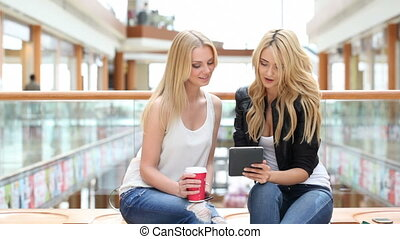 Women in mall using tablet