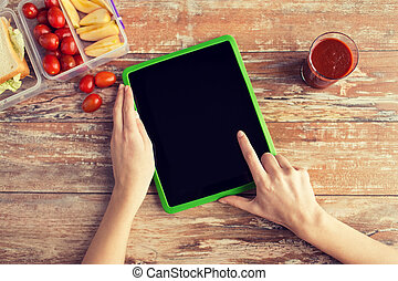 close up of woman with tablet pc food on table