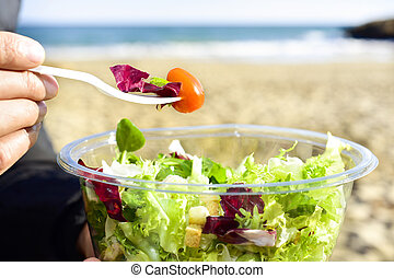 young man eating a prepared salad outdoors - closeup of a...