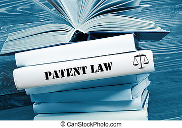 Book with Patent Law word on table in a courtroom or enforcement office. Toned image