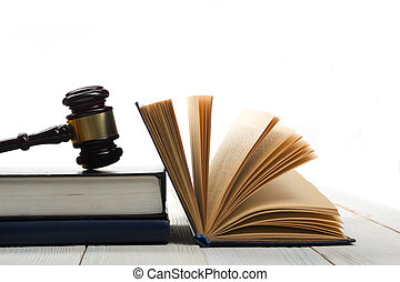 Open law book with wooden judges gavel on table in a courtroom