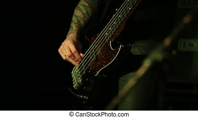 Bass guitar player close up playing virtuoso bass with...