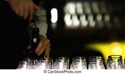 Picture of a young female bartender who is opening a bottle of wine with the corkscrew.