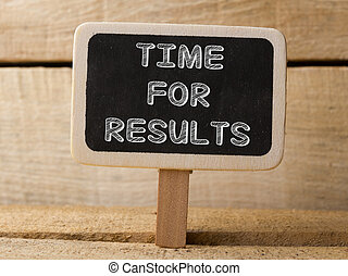 time for results concept on blackboard at wooden background...