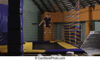 A young man in a T-shirt Jumping on a trampoline is...