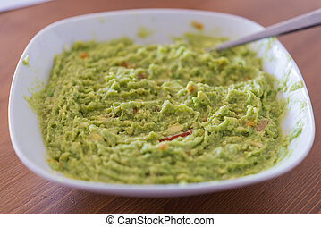 Aerial view closeup of homemade spicy guacamole dip served...