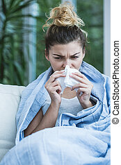 Woman suffering from flu blowing the nose