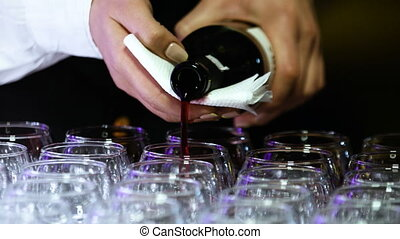 Young female sommelier with beautiful nail design is pouring...