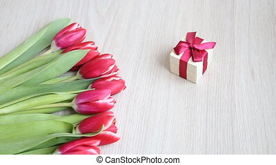 Red-white tulips on a white table move slowly out of the...