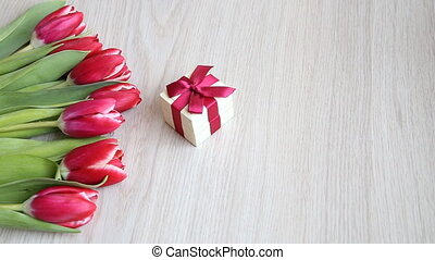 Tulips lay down next to the gift box with a red bow