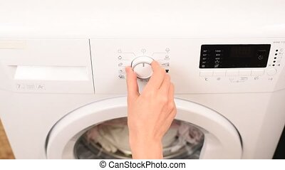 Starting White Modern Washing Machine by Woman Hand