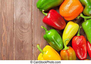 Fresh colorful bell peppers on wooden table Top view with...
