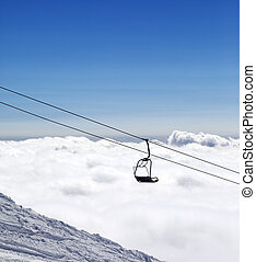 Ski slope, chair-lift and mountains under clouds Caucasus...