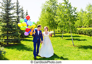 Beautiful bride and groom on a park with colorful balloons.