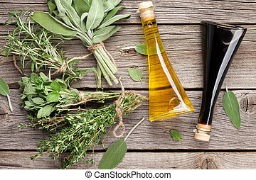 Fresh garden herbs and condiments on wooden table. Top view