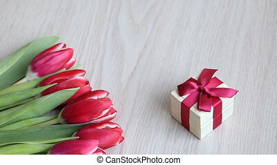Red-white tulips and gift with red bow are located on a...