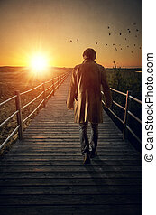 Boardwalk - A man with long coat walking in a boardwalk into...