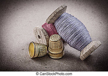 Spools of sewing threads thimbles on vintage background...