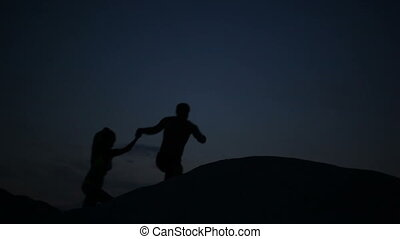 Romantic naked couple slowly climbing on the top of the hill in the pale blue twilight seluet