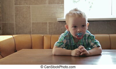 2 years old boy at an empty table