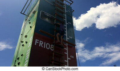 Girl climb on step ladder on a high vertical wall