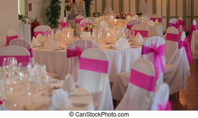 Decorated white and pink chairs and set tables in the...