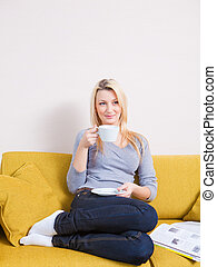 woman sitting on sofa and having coffee - woman sitting on...