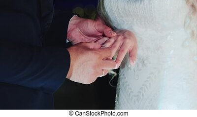 The bride wears a wedding ring on the groom
