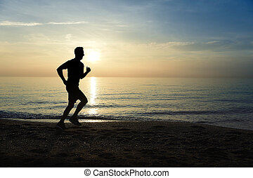 silhouette young sport man running outdoors on beach at...