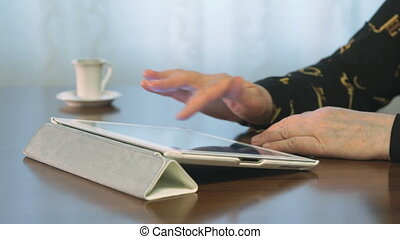 Woman works over documents using a digital tablet and drinks...
