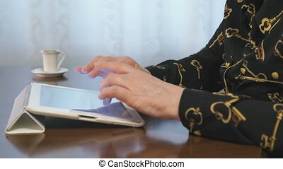 Woman works over documents using a digital tablet