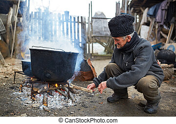 Old man fueling fire to boiling pots outdoor